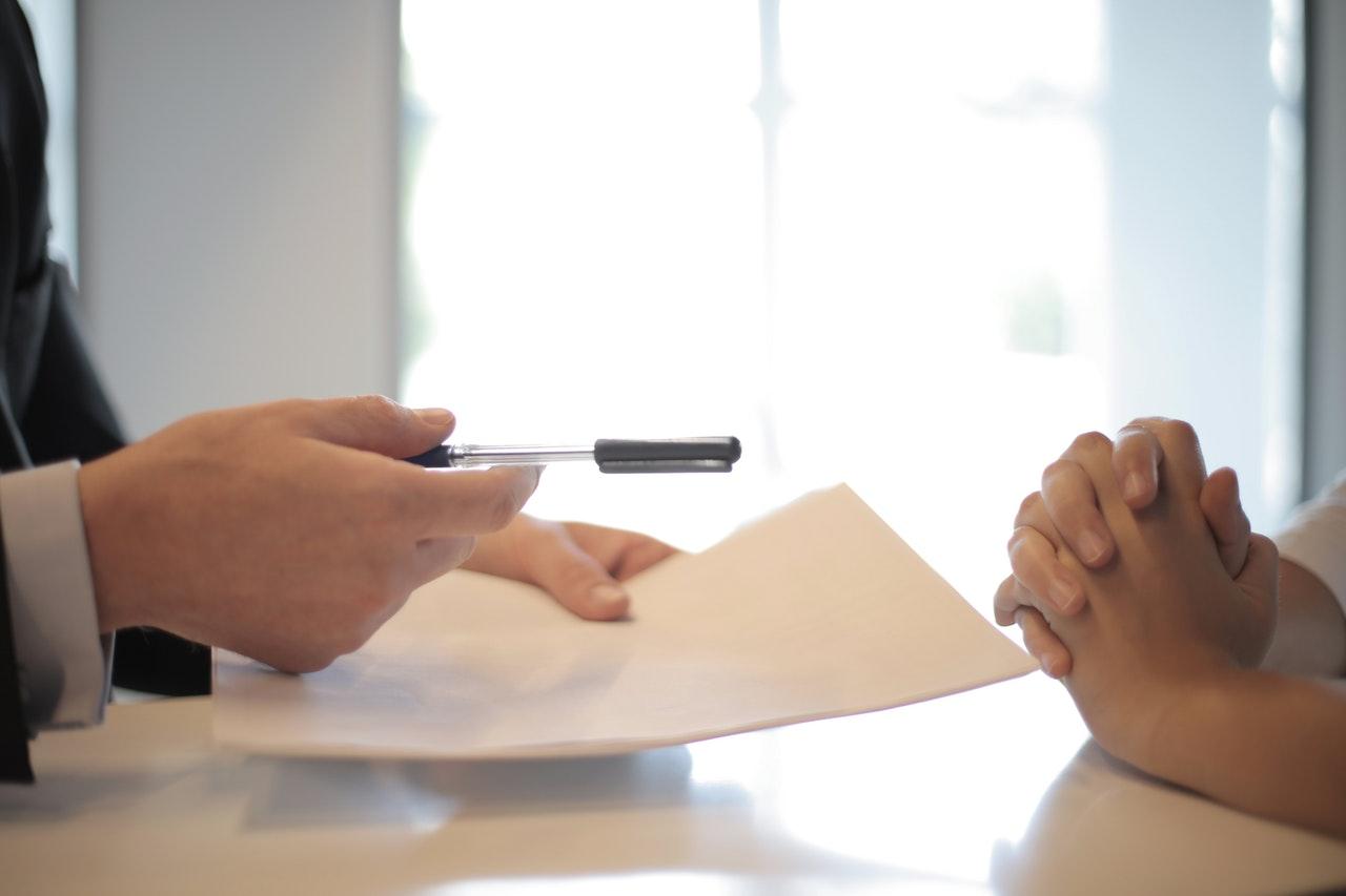 personne qui tient des documents dans une main et qui tend un stylo à une autre personne