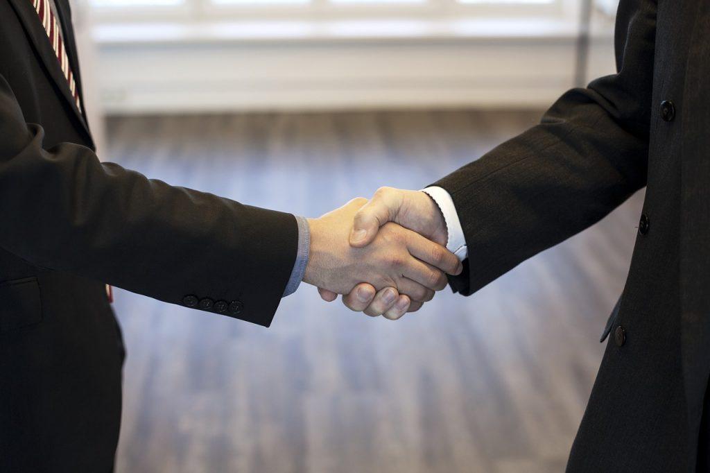 deux personnes en costume qui se serrent la main